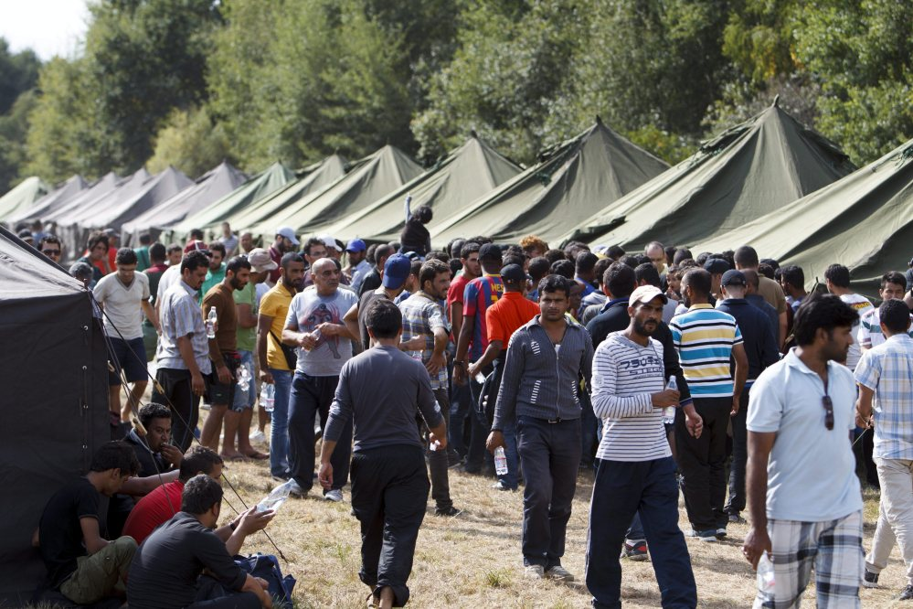 Migrants and refugees walk near tents tents at a collection point set up in Szentgotthard, near the Austrian border on Saturday.