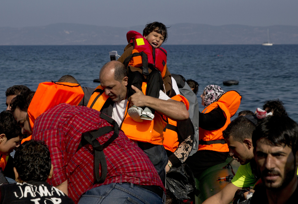 Migrants arrive aboard a dinghy after crossing from Turkey, to the island of Lesbos, Greece, on Sunday. A boat with 46 migrants or refugees has sunk Sunday in Greece and the coast guard says it is searching for 26 missing off the eastern Aegean island of Lesbos.