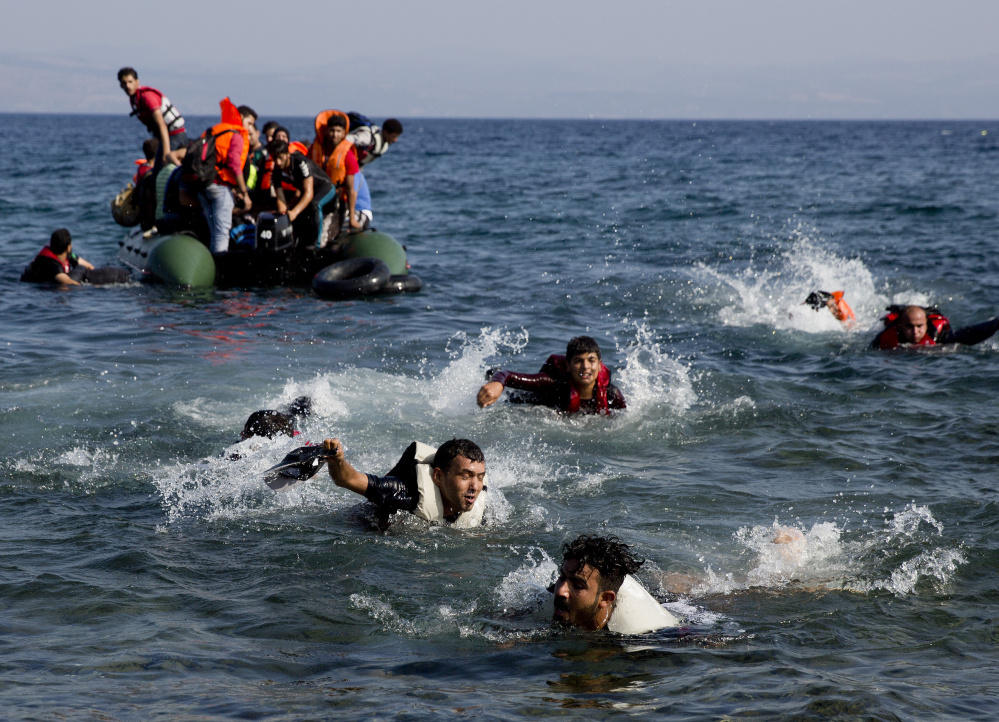 Migrants whose boat stalled at sea while crossing from Turkey to Greece swim toward shore off the island of Lesbos, Greece, on Sunday. A boat with 46 migrants sank off the coast of Greece and 26 people were missing.
