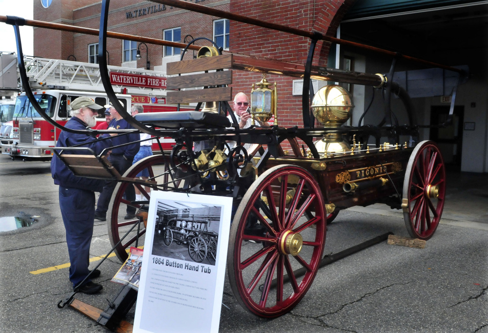 Dale Burnell, left, and David Bolduc look over an 1800s' horse-drawn hand pumper during an open house at Waterville Fire Department Central Station on Sunday.
