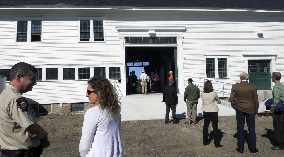 State officials gather Monday outside of the Campbell Barn in Augusta during a dedication ceremony for the renovated structure at the state complex on the city's east side.