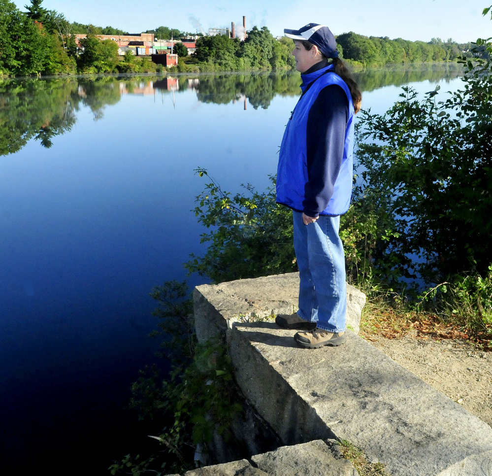Tina Richard stands on a granite abutment overlooking the Kennebec River along the Rotary Centennial Trail on Monday. The Huhtamaki mill is in background.