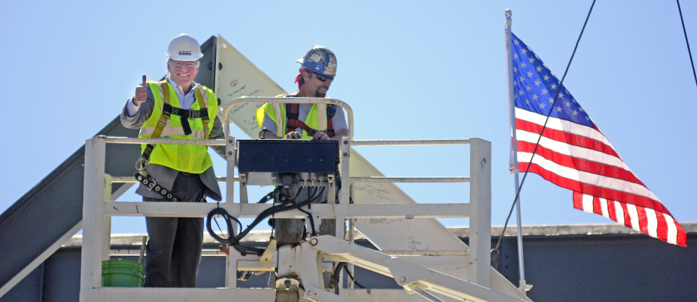 "Charles ""Wick"" Johnson, left, gives a thumbs up Monday after bolting a beam with ironworker Chris Cochran at the peak of the Lithgow Public Library in Augusta during a topping off ceremony."
