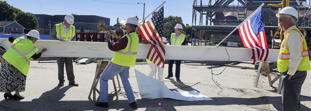 People sign an iron beam before it was placed at the peak of the addition Monday at Lithgow Public Library in Augusta during a topping off ceremony.