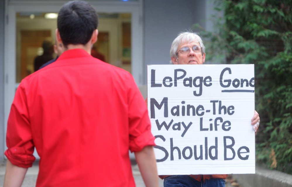 A protester leaves Preble Hall on Tuesday after showing his sign in opposition to Gov. Paul LePage before the governor took questions and delivered remarks to residents about his plan to move Maine forward at Thomas Auditorium at Preble Hall at the University of Maine at Farmington.