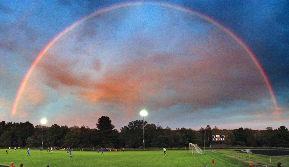 A rainbow glows of the Maranacook and Erskine boys teams during a soccer game Tuesday at The Ricky Gibson Field of Dreams in Readfield.