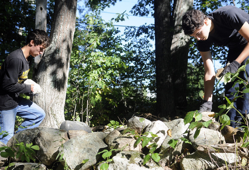 Maranacook Community High School juniors Taylor Anderson, right, and Ruslan Reiter put a stone wall together at the former Elizabeth Arden Estate, which is being renovated by the Travis Mills Foundation in Rome into a retreat for wounded veterans.