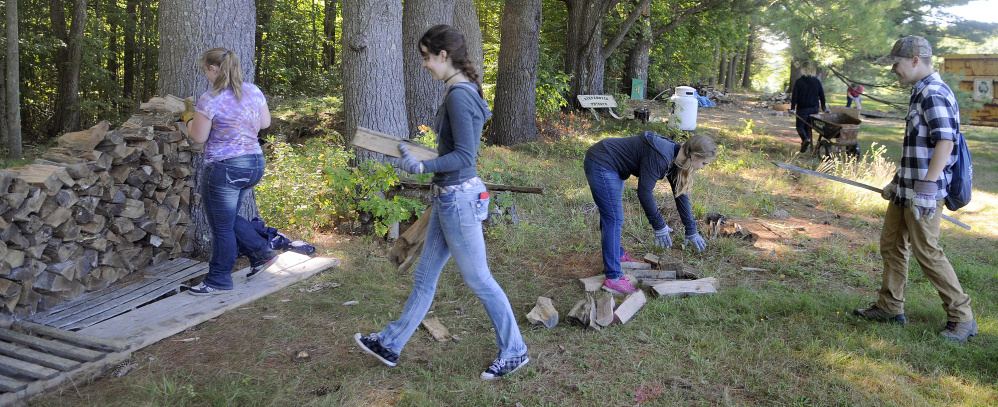 Maranacook Community High School juniors stack firewood Wednesday at the former Elizabeth Arden Estate, which is being renovated by the Travis Mills Foundation in Rome into a retreat for wounded veterans.