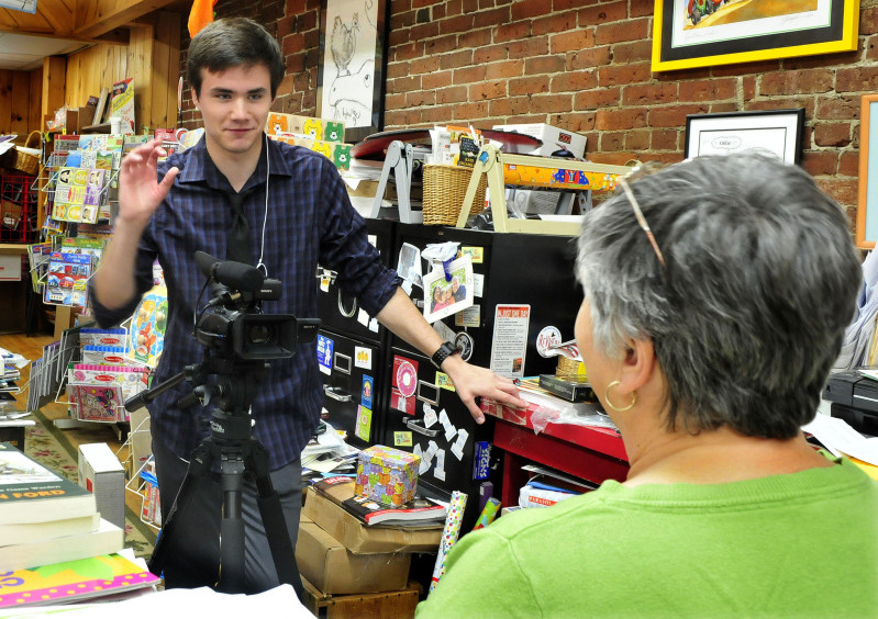 Mid-Maine Technical Center student Brad Calvin films Children's Book Cellar owner Ellen Richmond at the Waterville store on Wednesday as part of a project recording people, places and things in downtown Waterville.