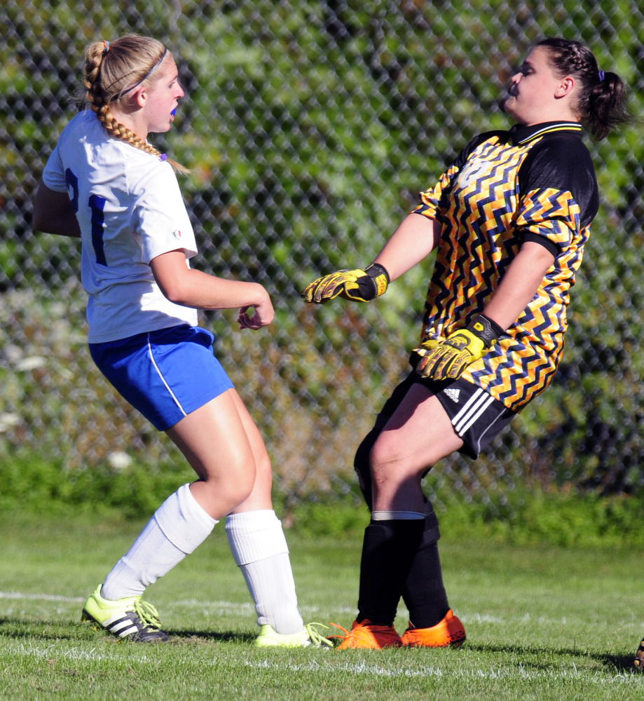 Oak Hill's Brittany Marquis (21), left, watches ball go into net behind Hall-Dale keeper Hailey Taker to make score 1-0 during a game Wednesday in Wales.