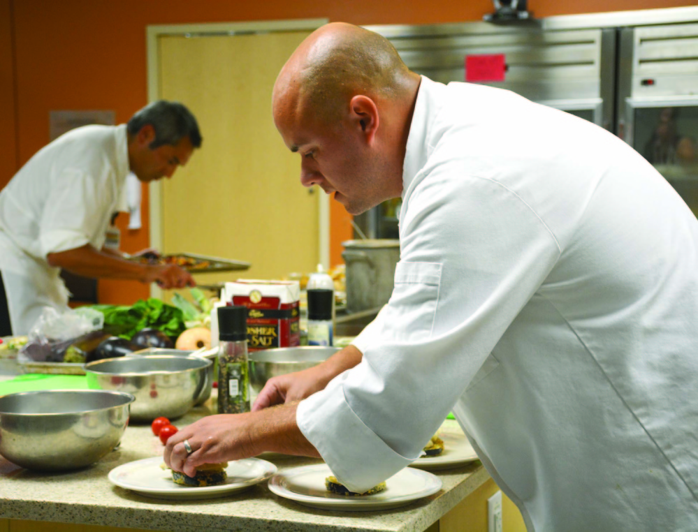 Blaine House executive chef Chris Hart, left, and MaineGeneral Food and Nutrition Services director Conrad Olin, right, plate their dishes before the judging at the Healthy Food Cook-Off.