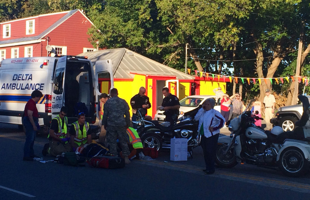 Emergency responders and onlookers gather around a two-motorcycle accident on College Avenue in Waterville Thursday evening. Diane and Michael Whalen, of Fairfield, were taken to the hospital after the three-wheeled motorcycle they were on rearended one driven by Glenn Whalen, Michael Whalen's brother.