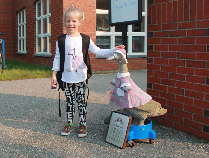 First-grader Khloie Caniff pets Georgie's head as second-grader Abigail Rogachoff walks by with a smile.