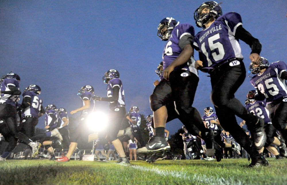 Members of the Waterville Senior High School football team run onto Drummond Field prior to a Big Ten Conference game Friday night against Oceanside. It marked the first night game in program history at Drummond Field.