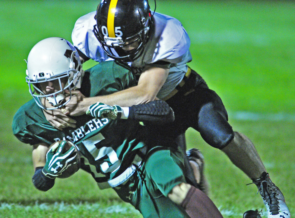 Staff photo by Joe Phelan   Winthrop/Monmouth's  Andrew Pazdziorko, left, gets taken down by Maranacook's Brandyn Michaud during a game Friday at Maxwell Field in Winthrop.