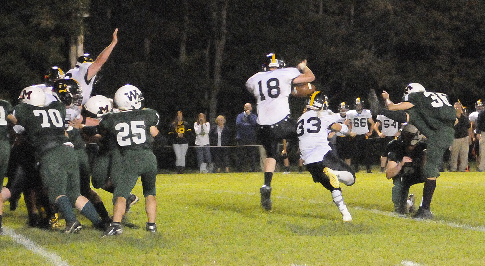 Staff photo by Joe Phelan   Maranacook's Jake Gibson (18) and Zach Lacasse block an extra point attempt by Winthrop/Monmouth kicker Tyler Cote during a game Friday night at Maxwell Field in Winthrop.