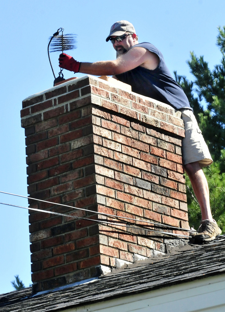 John Beane, of Complete Property Care Management Services, lifts a weighted chimney brush to clean a homeowner's chimney on Thursday.