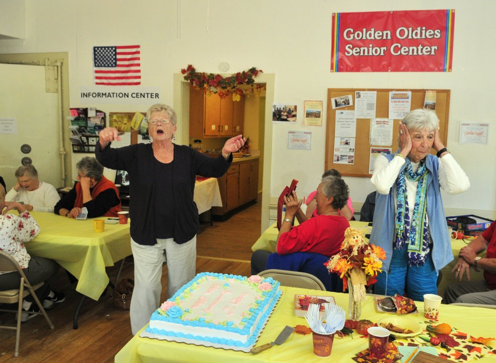 Staff photo by Joe Phelan Before she cuts the cake, Bette Horning, left, does a Tiny Tim impersonation as Betty Sawyer covers her ears in mock horror Saturday during a 10th-anniversary party for the Golden Oldies Senior Center in Richmond.