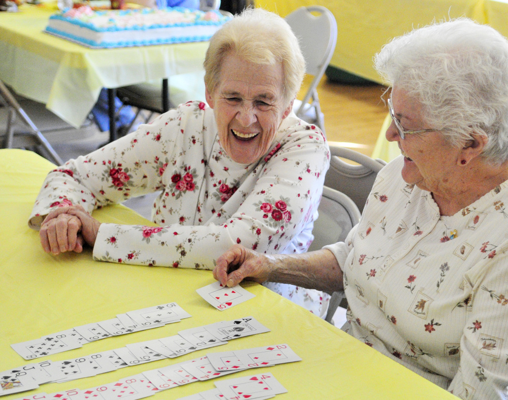 Joyce Pinkham, left, and Dorothy Wallace laugh as they play cards Saturday during a 10th-anniversary party for the Golden Oldies Senior Center in Richmond.