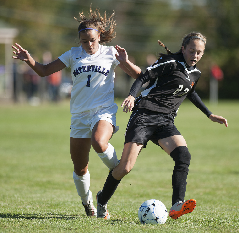 Kevin Bennett photo   Waterville's Mackenzie St. Pierre trips while battling for control of the ball with Winslow's Maeghan Bernard on Saturday at Waterville.