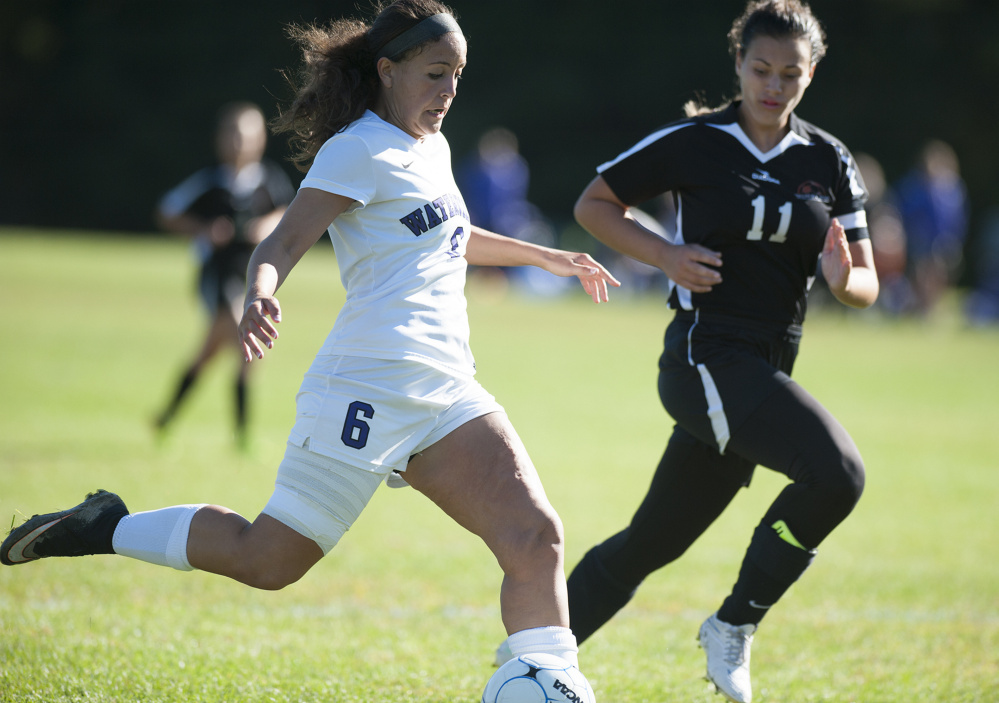 Photo by Kevin Bennett   Waterville's Fotini Shanos, left, takes a shot on goal while being closely defended by Winslow's Madison Morneault on Saturday at Waterville.