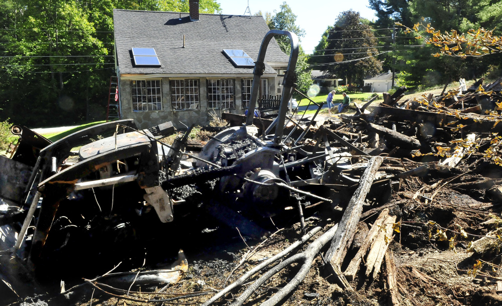 Laurie and Rick Vigue, background, take a break beside the burned remains of their barn on Sunday. Fire destroyed the 60-year-old barn and did minor damage to the Vigues' home in Winslow. They lost a brand new tractor in the foreground.