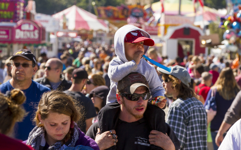 Ryon Harris, 3, gets an elevated view from atop his uncle Scott LeGrace's shoulders Sunday at the Cumberland fair.