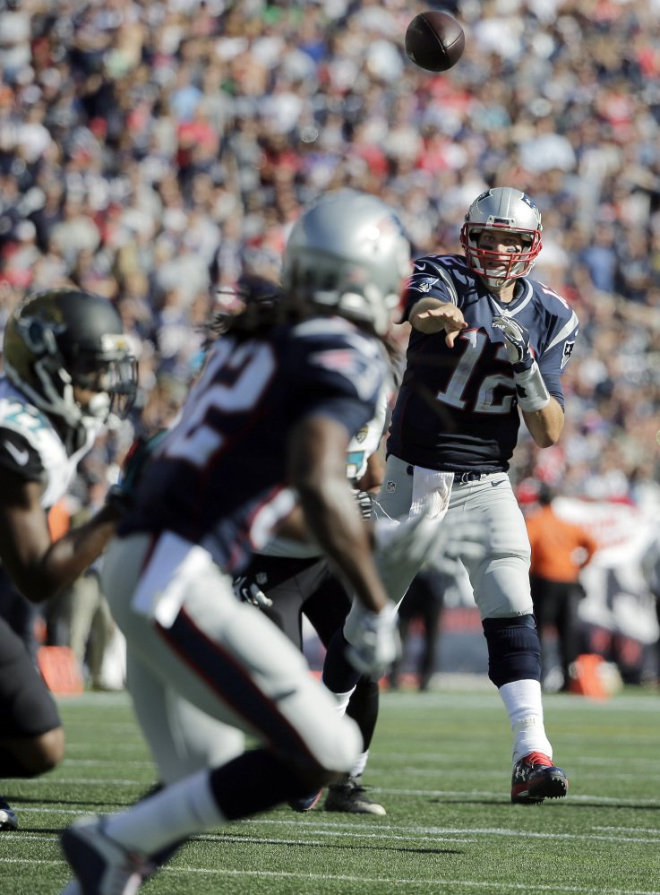 New England Patriots quarterback Tom Brady (12) throws a touchdown pass to wide receiver Keshawn Martin, foreground, in the second half against the Jacksonville Jaguarson Sunday, in Foxborough, Mass.