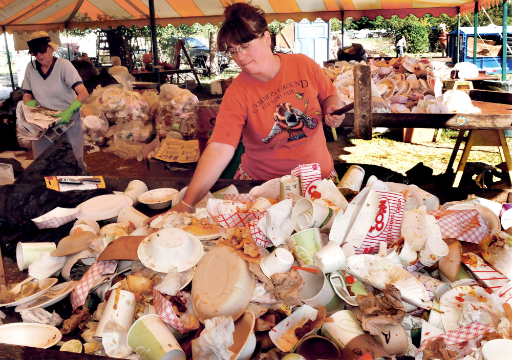 Lisa Willey, coordinator of the compost and recycling site at the Common Ground Country Fair in Unity, sorts through collected material for compost and items that can be re-used on Sunday.