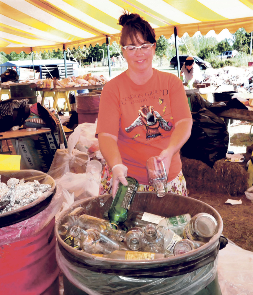 Lisa Willey, coordinator at the compost and recycling site at the Common Ground Country Fair in Unity, sorts glass and metals for recycling on Sunday.