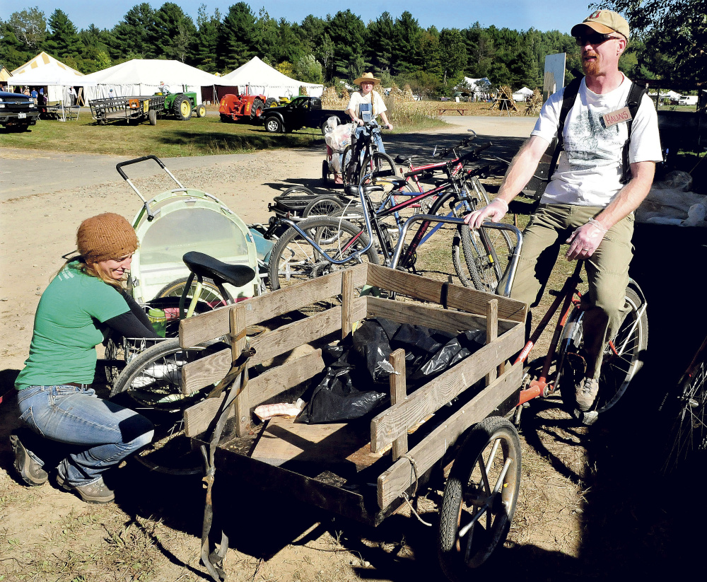 Volunteers collect bags of material on bike trailers that will be either composted or recycled at the Common Ground Country Fair in Unity on Sunday. From left are Kendall Hinkley, Thea Youngs and Hauns Bassett.