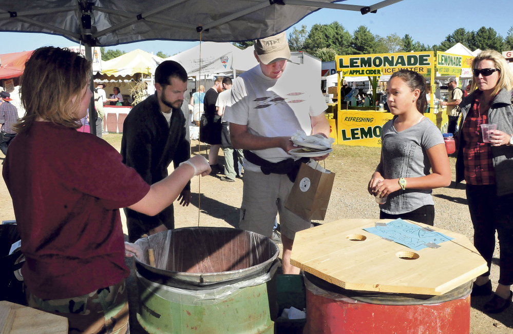 Paul Millard, center, decides which material goes into different containers to be either recycled or composted at the Common Ground Country Fair in Unity on Sunday. At left is volunteer Aiden Childs, who assisted fairgoers.