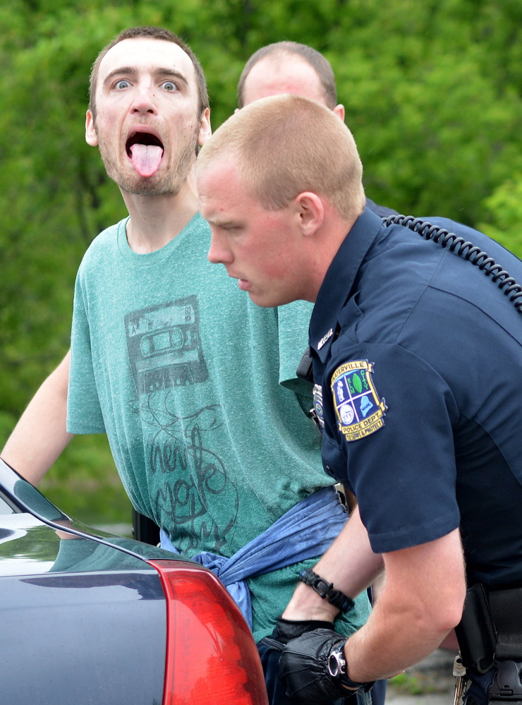 Waterville officer Chase Fabian, foreground, frisks Jesse J. Peterson at Head of Falls in Waterville in this June file photo.
