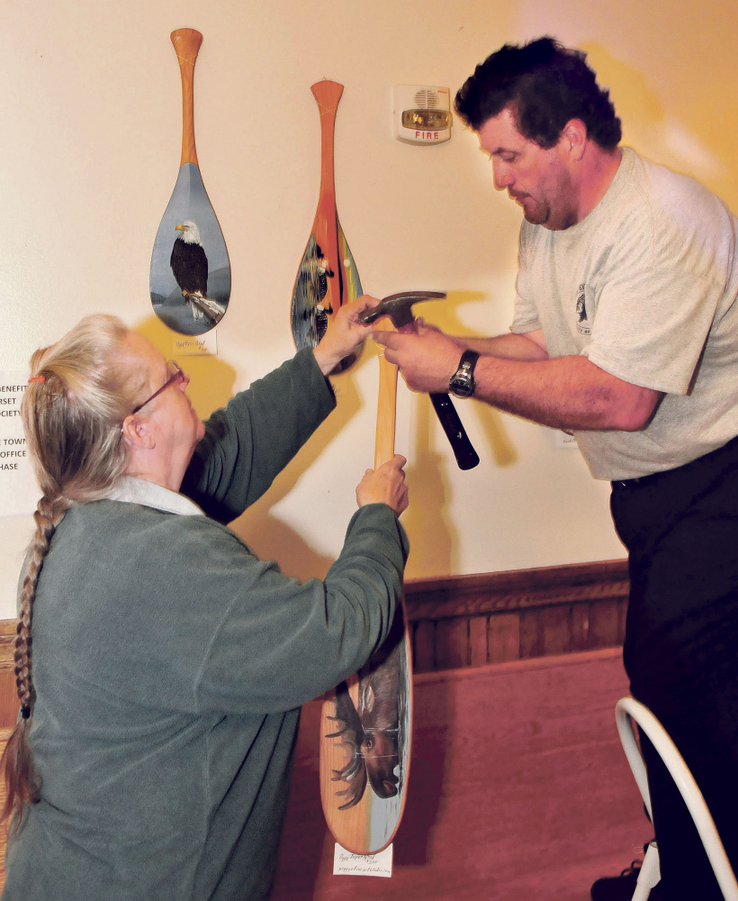 Artist Peggy Tozier Graf hands a painted paddle up to Dayson Davis for him to hang with other artists work in the Skowhegan Municipal Building on Tuesday, Proceeds from sale of the art by current and former students and teachers of the Skowhegan Adult Education program go to the Somerset Humane Society.