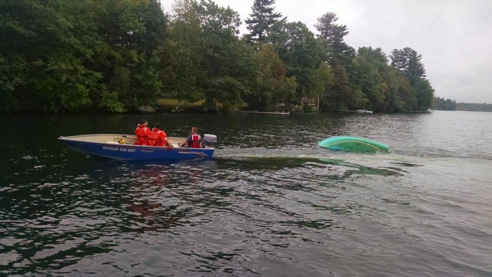 Winthrop fire and rescue crews assist Monmouth firefighters in towing a capsized sailboat Tuesday from Cochnewagon Lake in Monmouth.