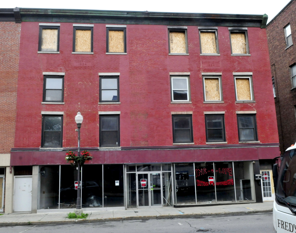 An apartment building and former pawn shop remain boarded up and vacant since fire heavily damaged the building on Main Street in Waterville.