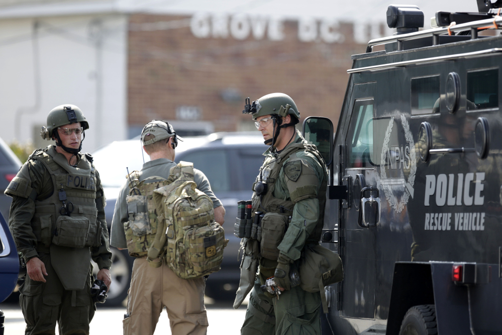 Police officers gather before heading out for a manhunt after an officer was shot in Fox Lake, Ill., on Tuesday.