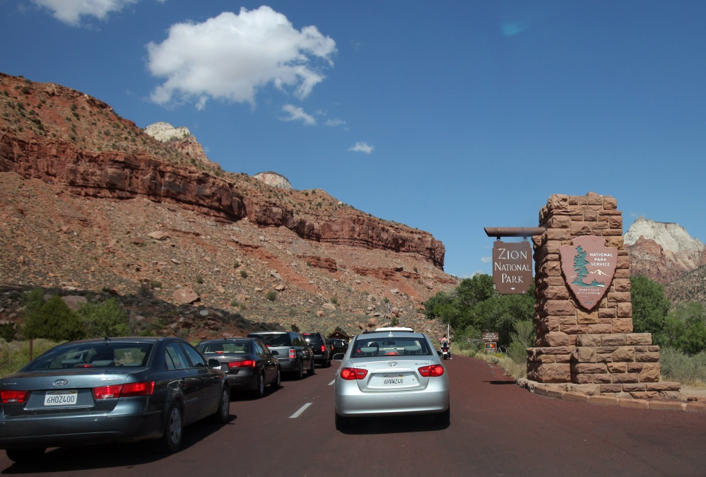 Long lines of cars wait to enter the southern entrance to Zion National Park in Utah. The National Park Service already has recorded 5 million more visitors from this time last year, creating traffic congestion, long waits, and crowded parks.