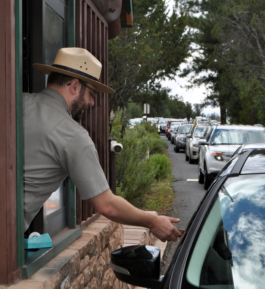 Nate Powell collects entrance fees Aug. 2 as many cars wait in line to enter Grand Canyon National Park. Visitation there is up nearly 30 percent over last year.