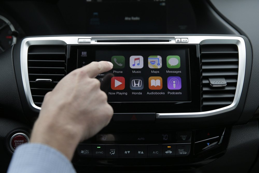 Apple's CarPlay system, at left, and Google's Android Auto will be installed in many cars, including some affordable 2016 models.