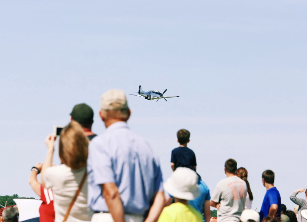 Audience members watch as a P-51 Mustang flies past during the beginning of the Airshow at Brunswick landing on Saturday.