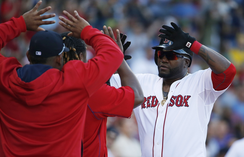 Boston Red Sox's David Ortiz, right, celebrates his solo home run during the fourth inning of a baseball game against the Philadelphia Phillies in Boston, Saturday.