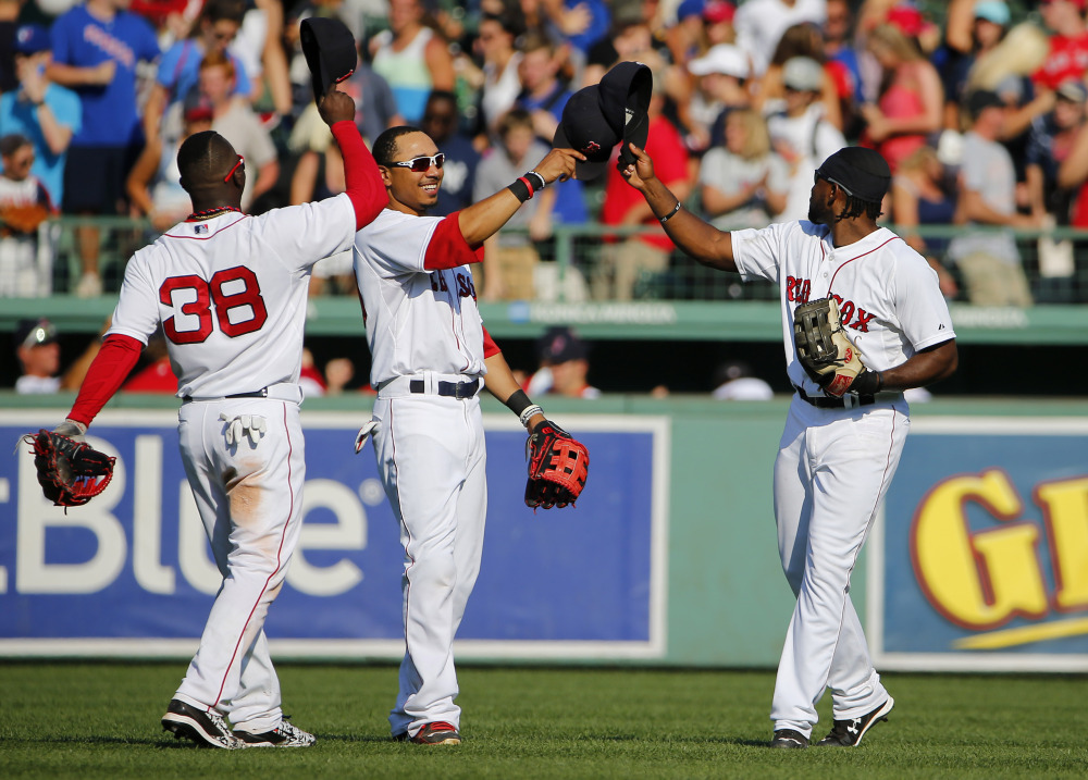 Red Sox outfielders, left to right, Rusney Castillo, Mookie Betts and Jackie Bradley Jr. celebrate after Boston's 11 win over the Toronto Blue Jays on Monday at Fenway Park.
