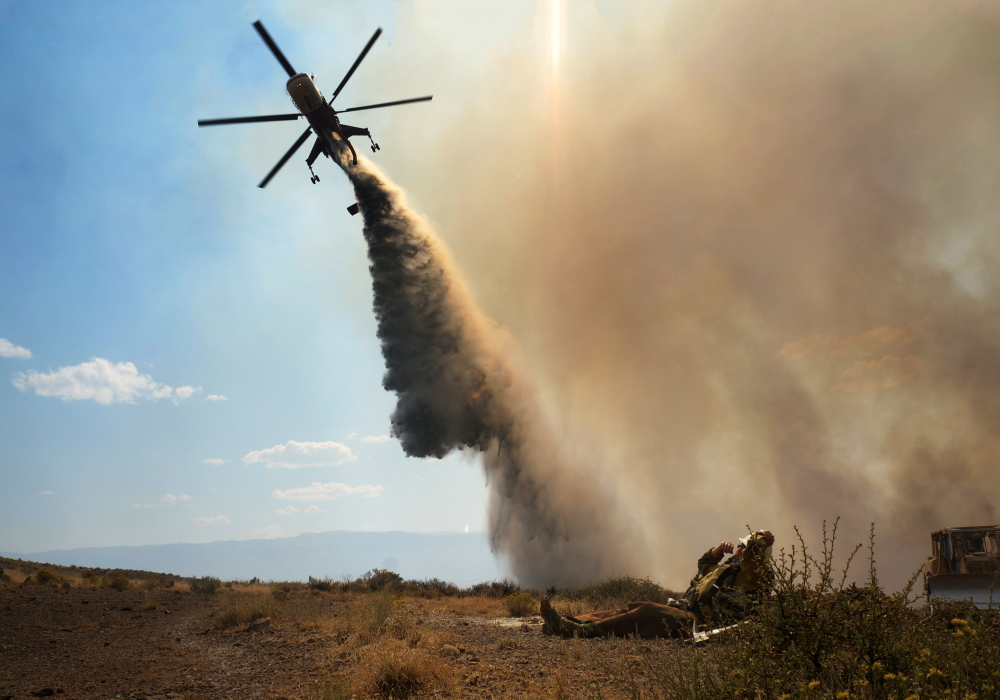 This Aug. 9, 2015 photo taken by Utah state firefighter Eli Peterson shows a firefighter watching as a helicopter makes a water drop over a fire in Owyhee County, Idaho.