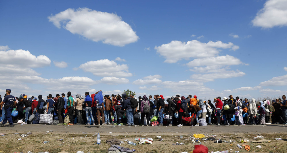 People wait in a queue for buses at a temporary holding center for migrants near the border line between Serbia and Hungary in Roszke, southern Hungary, Wednesday.
