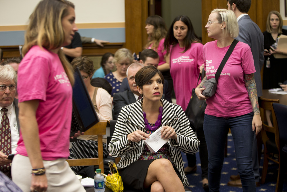 As supporters of Planned Parenthood looks for seats, anti-abortion activist Melissa Ohden, center, waits to testify before the House Judiciary Committee hearing at the Capitol in Washington examining the abortion practices of Planned Parenthood.