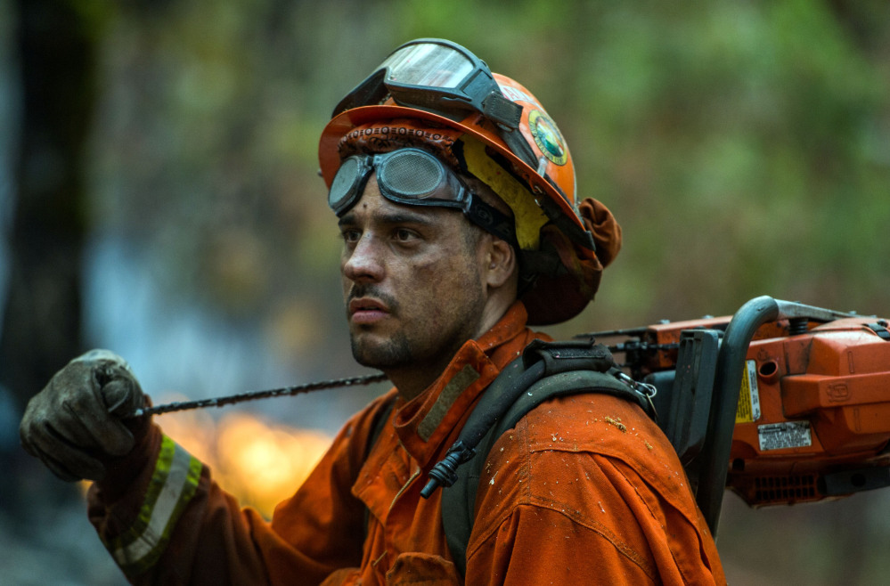 A fire crew member inspects a spot fire near Glencoe, Calif., on Friday.