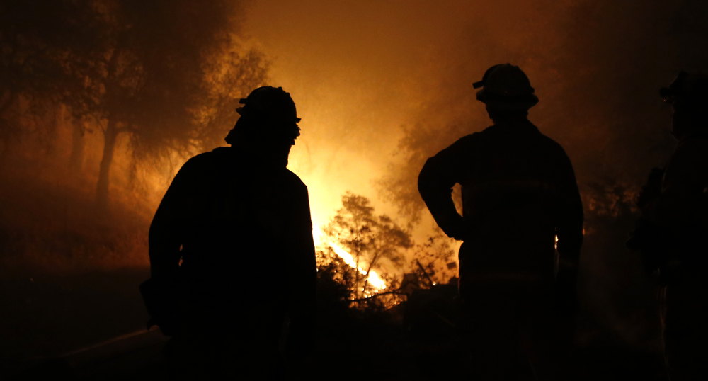 Firefighters watch as the flames of the Butte Fire approach a containment line near San Andreas, Calif.,  on Friday. The Associated Press