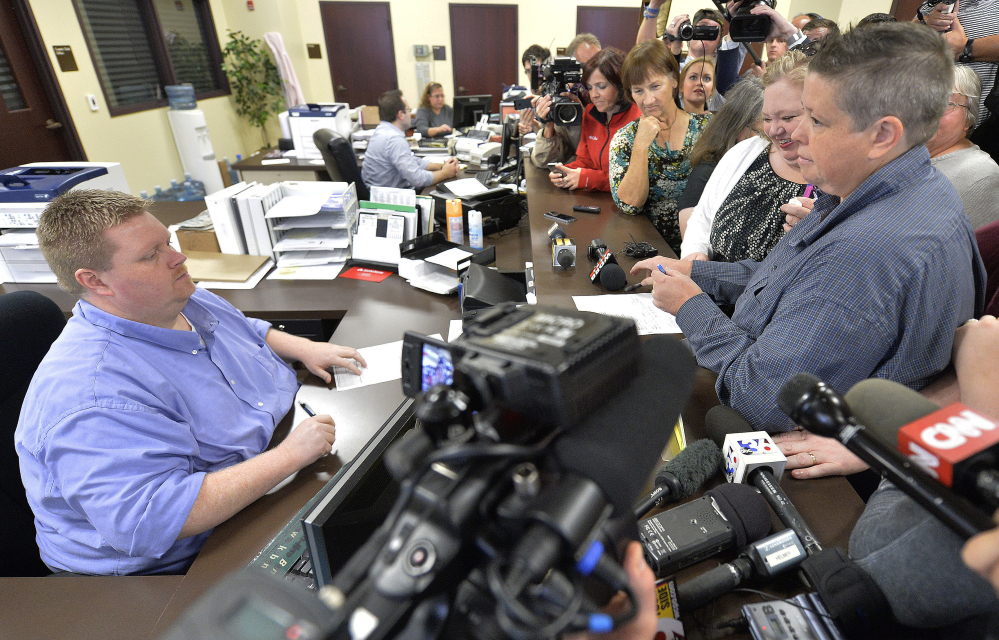 """Rowan County Deputy Clerk Brian Mason, left, now given the job title, """"marriage license deputy,"""" helps Shannon Wampler-Collins, right, and Carmen Wampler-Collins with a marriage license."""