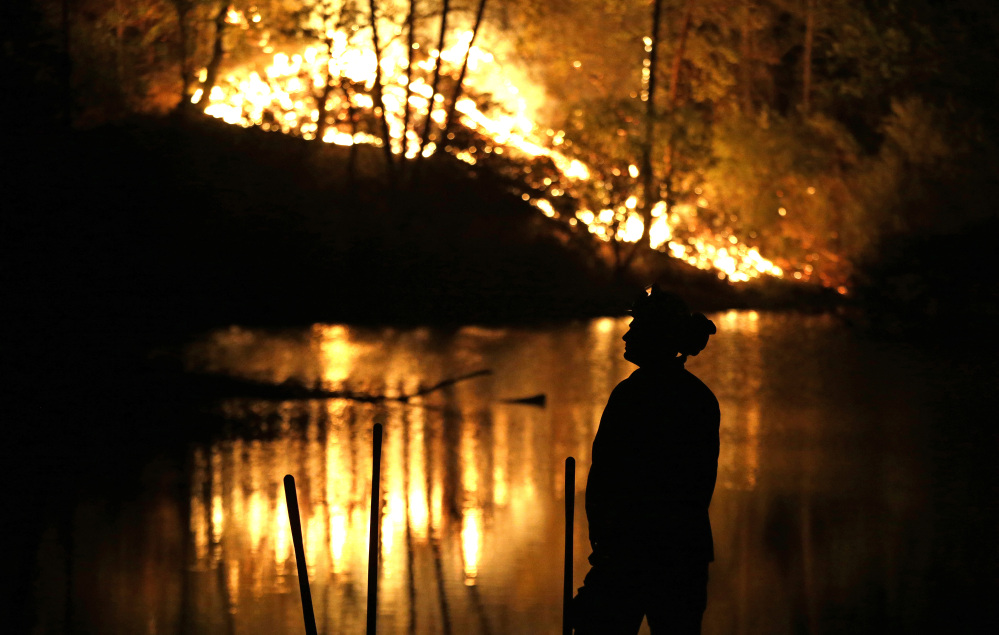 A firefighter stands near a wildfire in Middletown, Calif., on Sunday. Two of California's fastest-burning wildfires in decades overtook several Northern California towns.